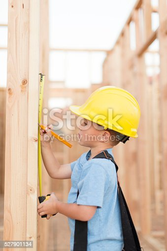 527687520 istock photo Young Boy dressed as Carpenter with Tape Measure 527901134