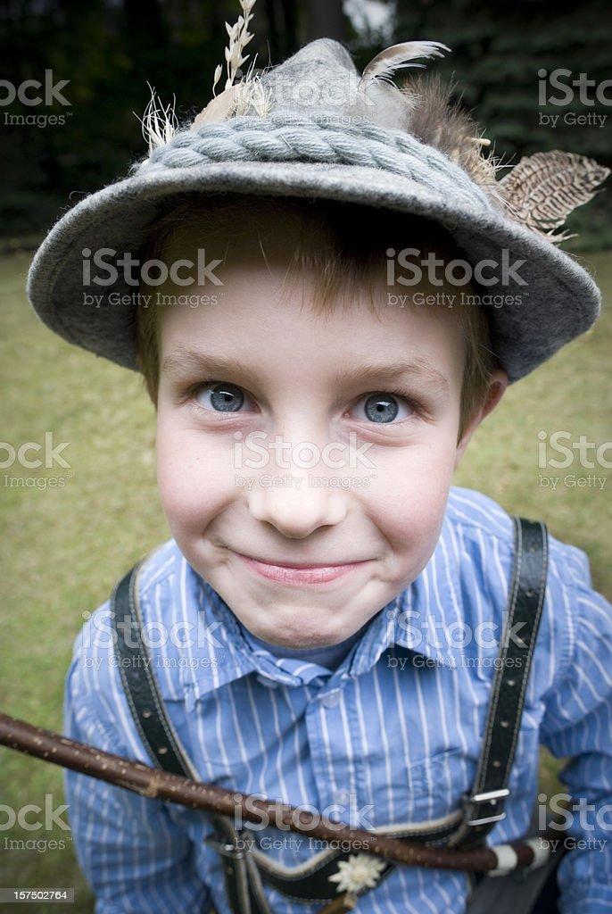 Young boy dressed as hunter, wearing felt hat, bow, lederhosen royalty-free stock photo
