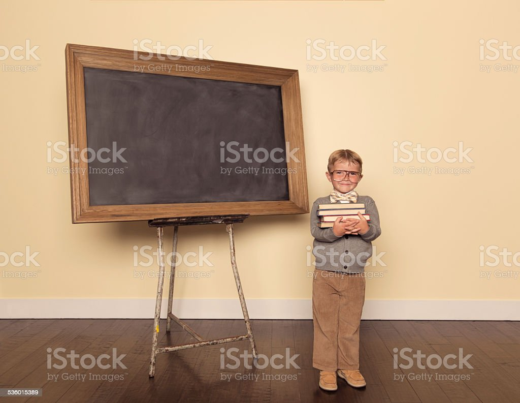 Young Boy Dressed as Nerd at Chalkboard Holding Books stock photo