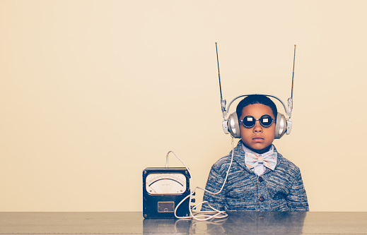 A young boy imagines reading mind and receiving communications from outer space with a homemade science project on his head. He is dressed in casual clothing, glasses and bow tie. He is wearing headphones in front of a beige background with a serious expression waiting. Retro styling.