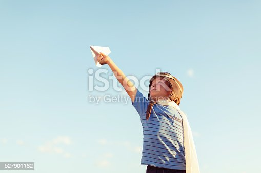 A young boy wearing a flight cap and aviator goggles holds up a paper airplane to the clear sky in hopes of flying. There is plenty of blue sky for copy space.