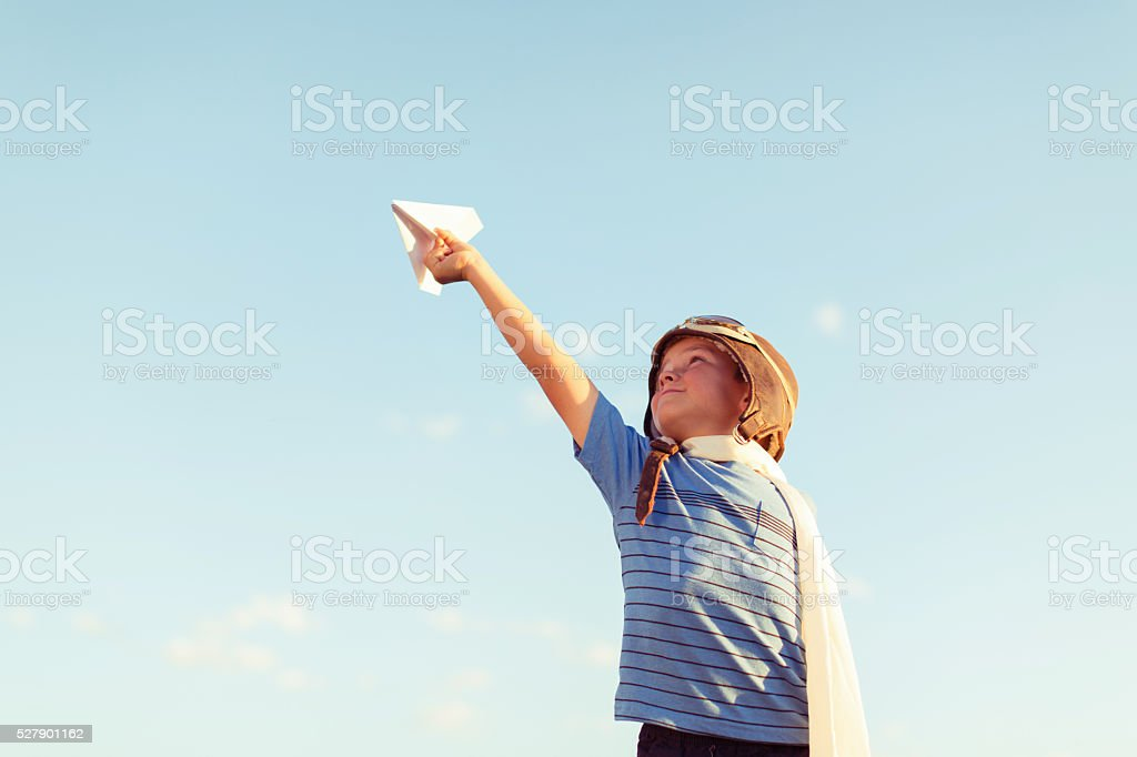 Young Boy Dressed as Pilot Flies Paper Airplane stock photo