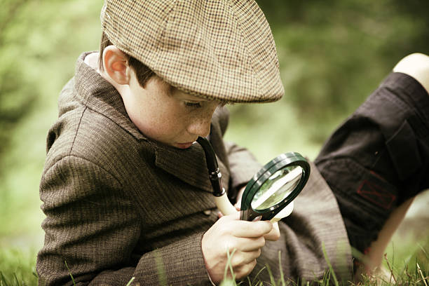 young boy dressed as sherlock holmes using magnifying glass - sherlock holmes stock photos and pictures