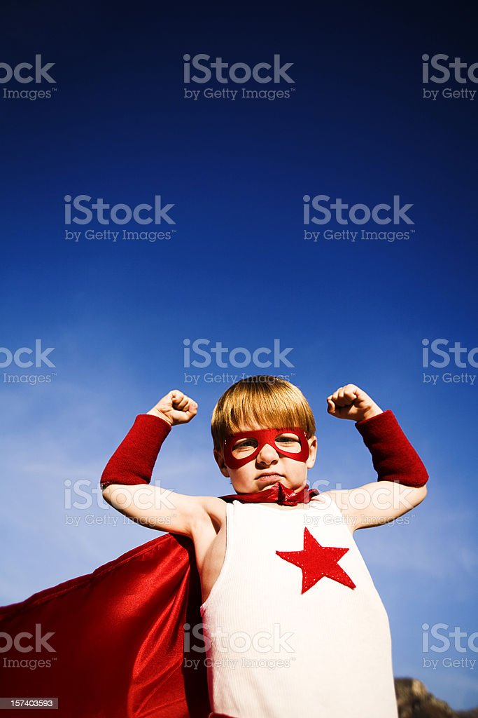 Young Boy Dressed as Superhero flexes Muscles royalty-free stock photo