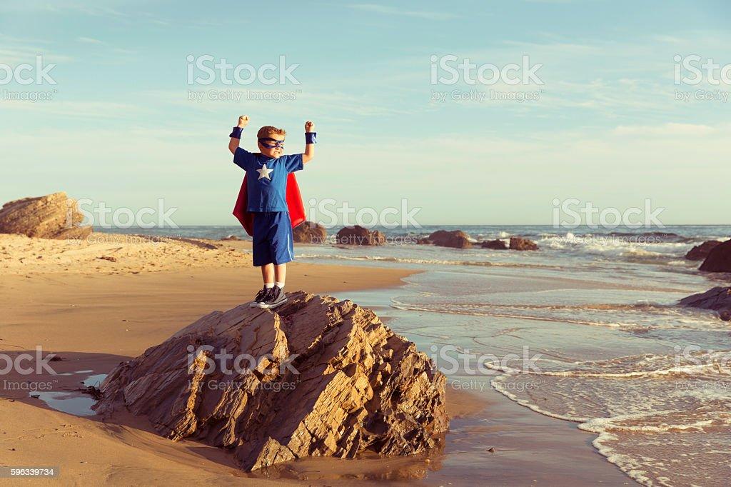 Young Boy Dressed as Superhero Flexes Muscles Lizenzfreies stock-foto