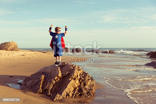 istock Young Boy Dressed as Superhero Flexes Muscles 596339734