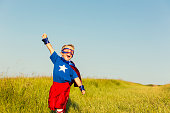 A young boy wearing a superhero cape and mask is ready to face life's challenges with confidence. He has his arm raised to the sky while standing in tall grass. Image taken in Wiltshire, United Kingdom.