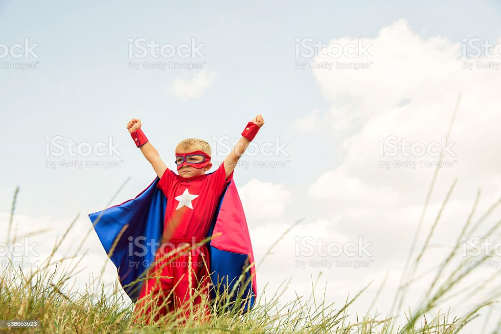 Young Boy dressed as Superhero Raises Arms in Park stock photo