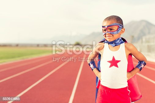 A young boy dressed up as a superhero gets ready to run fast on a track. Even superheroes have to train.