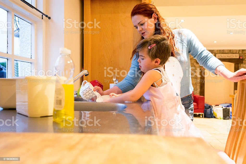 Young Boy Dressed in a Fairy Costume Doing Chores stock photo