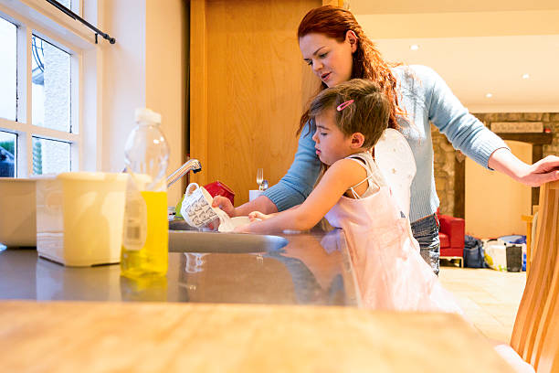 Young Boy Dressed in a Fairy Costume Doing Chores Little boy stands at the kitchen sink washing up. He is concentrating as a woman stands at the side to help. transgender stock pictures, royalty-free photos & images