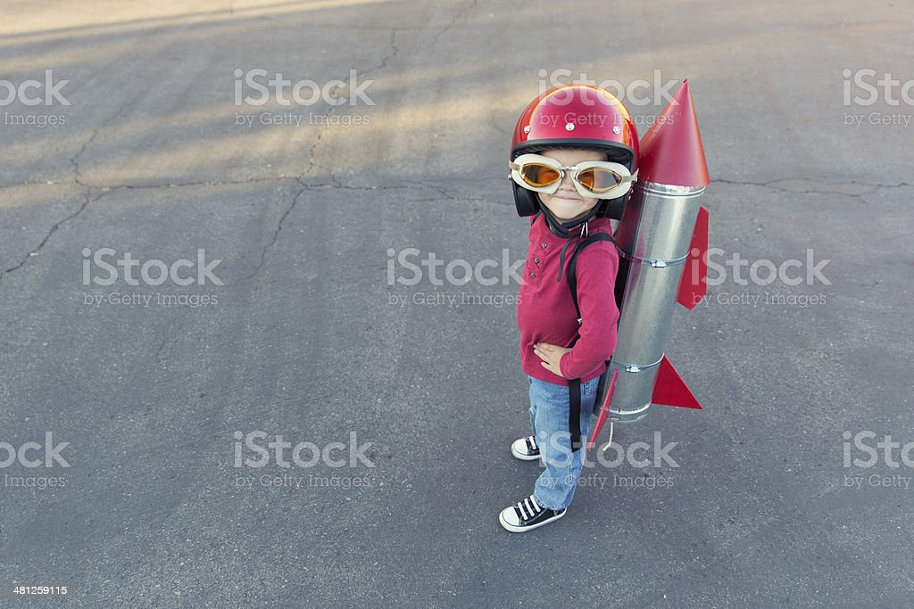 Young boy dressed in a red rocket suit on blacktop A young boy is ready to go places with a rocket strapped on his back. 4-5 Years Stock Photo
