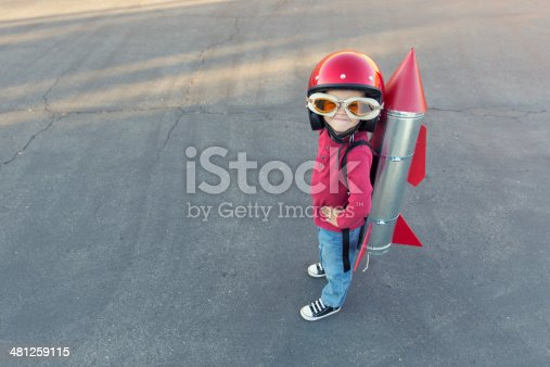 istock Young boy dressed in a red rocket suit on blacktop 481259115