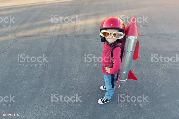 Young Boy Dressed In A Red Rocket Suit On Blacktop Stock Photo - Download Image Now