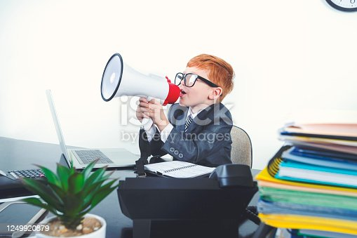 istock Young boy dressed in a suit working at a large desk. 1249920879
