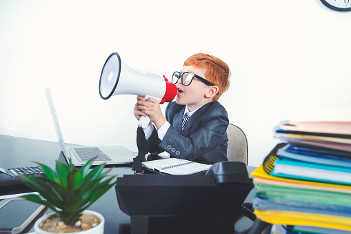 623763462 istock photo Young boy dressed in a suit working at a large desk. 1249920879