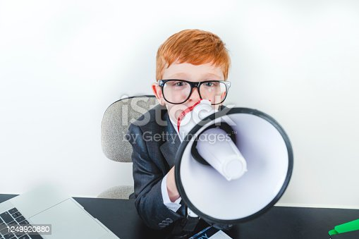 istock Young boy dressed in a suit working at a large desk. 1249920880