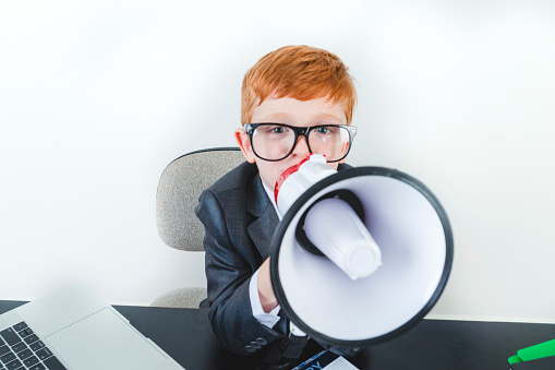 623763462 istock photo Young boy dressed in a suit working at a large desk. 1249920880