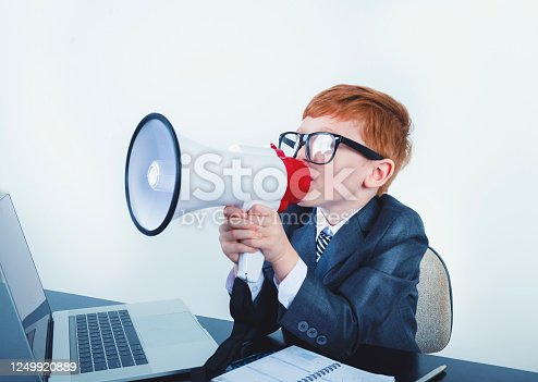 istock Young boy dressed in a suit working at a large desk. 1249920889
