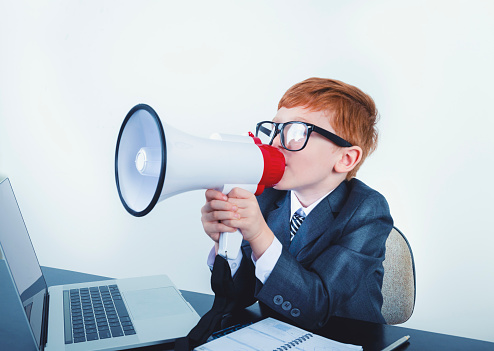 623763462 istock photo Young boy dressed in a suit working at a large desk. 1249920889