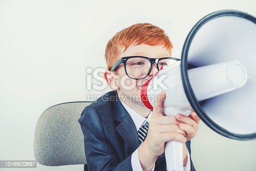 istock Young boy dressed in a suit working at a large desk. 1249920897