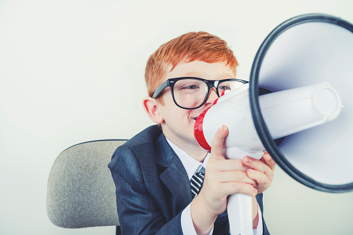 623763462 istock photo Young boy dressed in a suit working at a large desk. 1249920897
