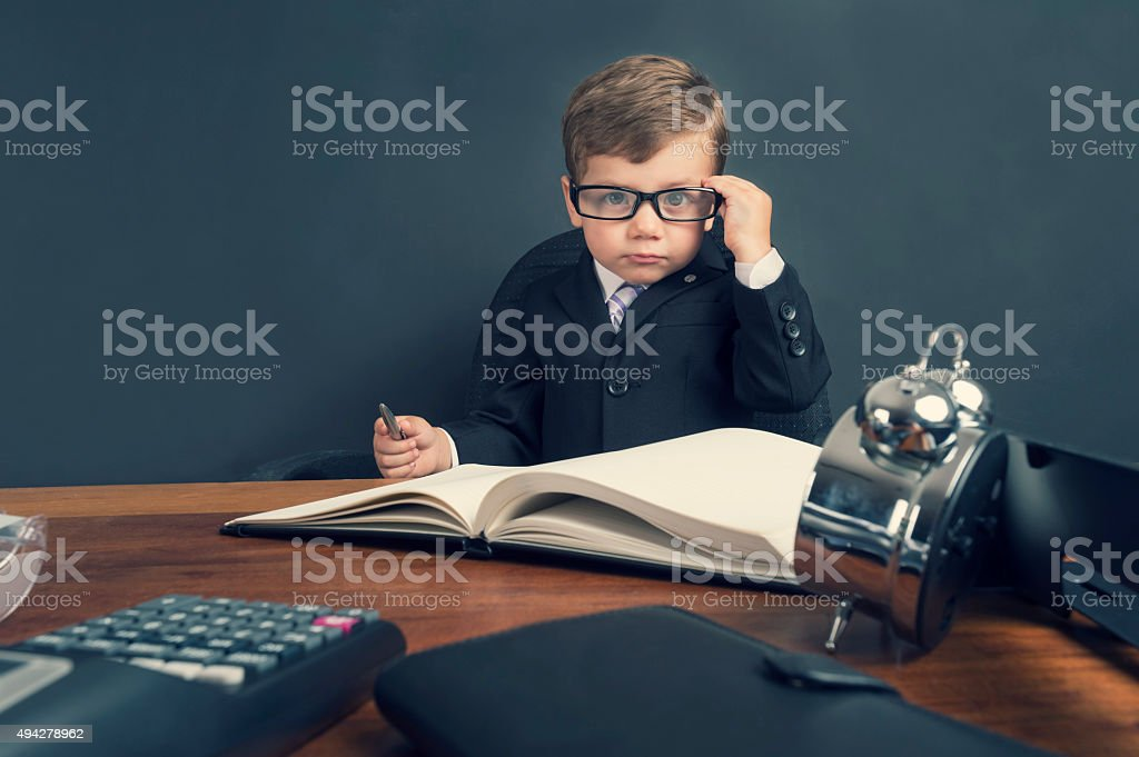 Young boy dressed in suit working at desk. stock photo