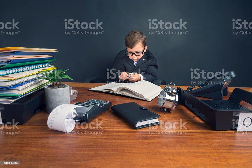 Junge gekleidet in Anzug Arbeiten am Schreibtisch. Lizenzfreies stock-foto