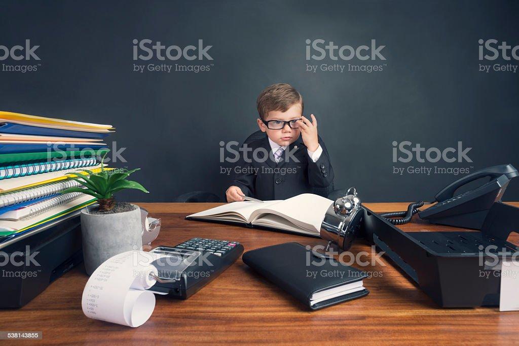 Photo de jeune garçon habillé en costume travaillant au bureau