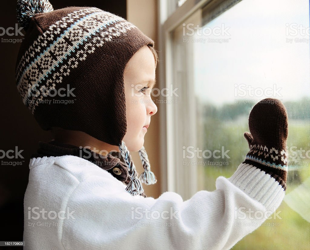 Young boy dressed warmly staring out of a window royalty-free stock photo