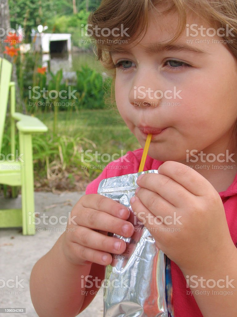 A young boy drinking a juice pouch through a straw royalty-free stock photo