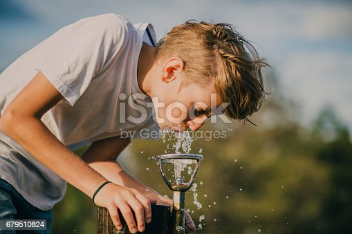 Young boy drinking from a water fountain in a park in Melbourne, Australia.