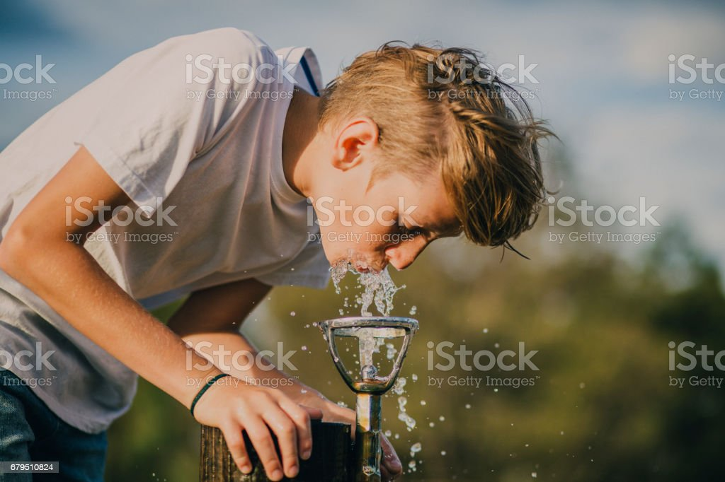 Young Boy Drinking from a Water Fountain stock photo