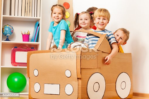 istock Young boy driving his friends in cardboard car 539855596