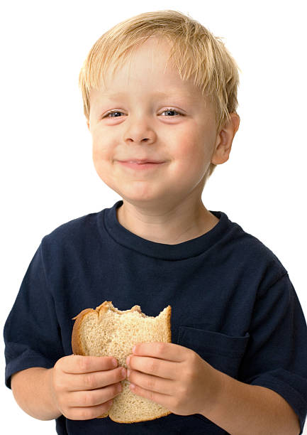Young boy eating a peanut butter sandwich stock photo