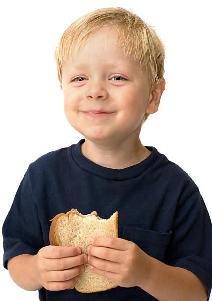 Young boy eating a peanut butter sandwich