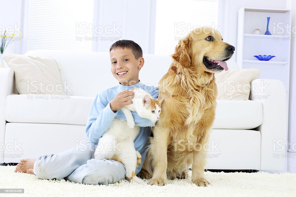 Young boy enjoys with pets, embracing cat. royalty-free stock photo