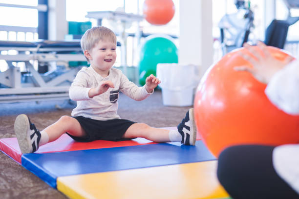 Young boy exercising in physiotherapy clinic stock photo