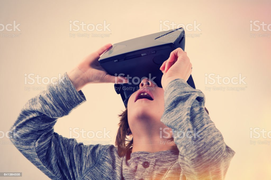 Young Boy Experiencing Virtual Reality A 6 year old boy watching a virtual reality movie on a VR headset. 6-7 Years Stock Photo