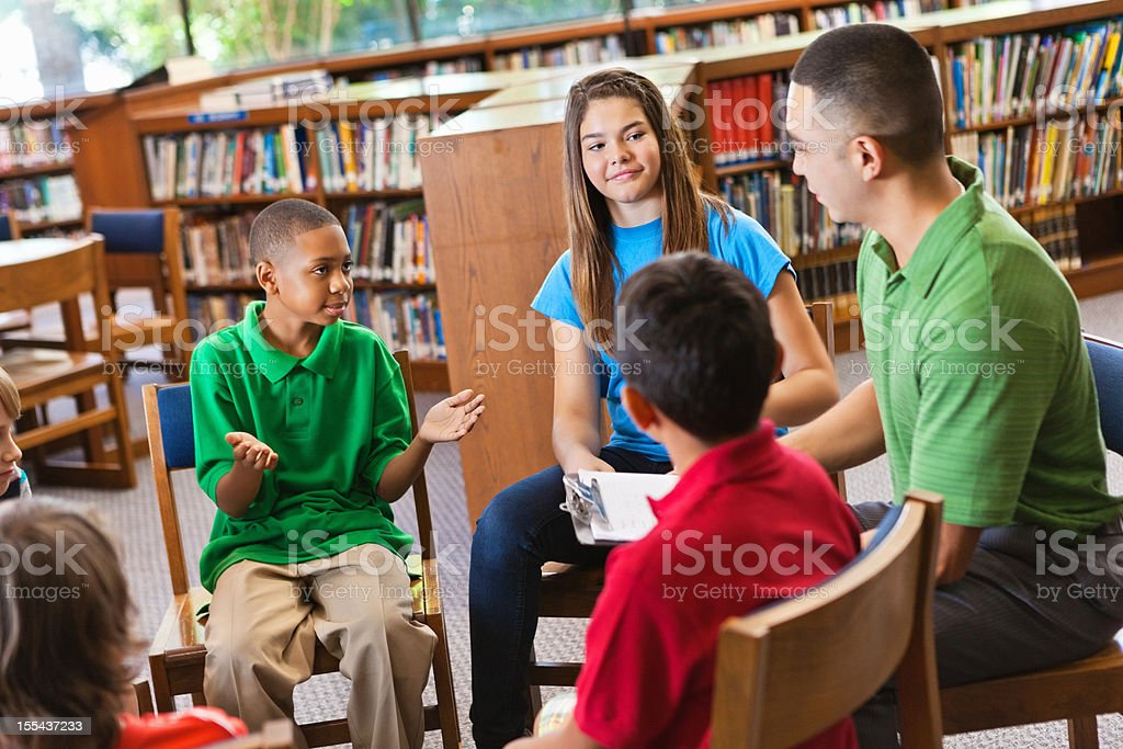 Young boy explaining something to classmates in the school library royalty-free stock photo