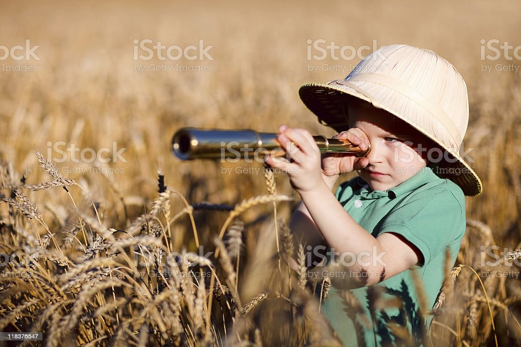 A young boy exploring nature with a telescope stock photo