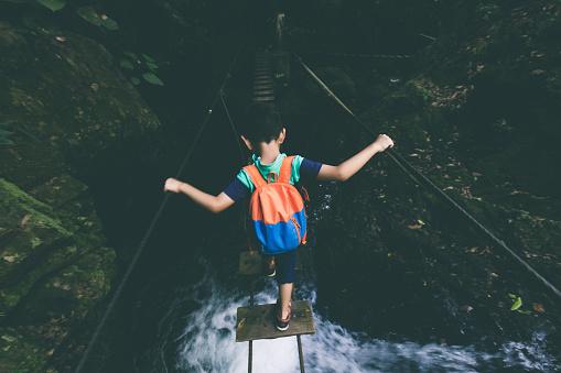 Young boy exploring through single-plank bridge