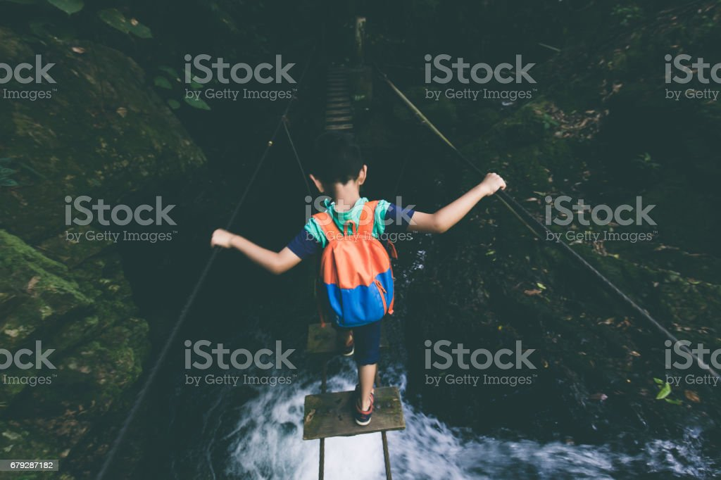 Young boy exploring through single-plank bridge stock photo