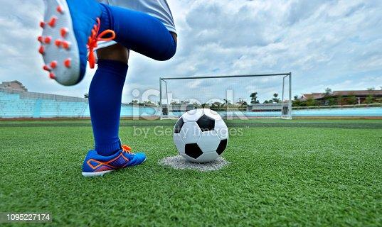 Young boy feet kicking a soccer ball