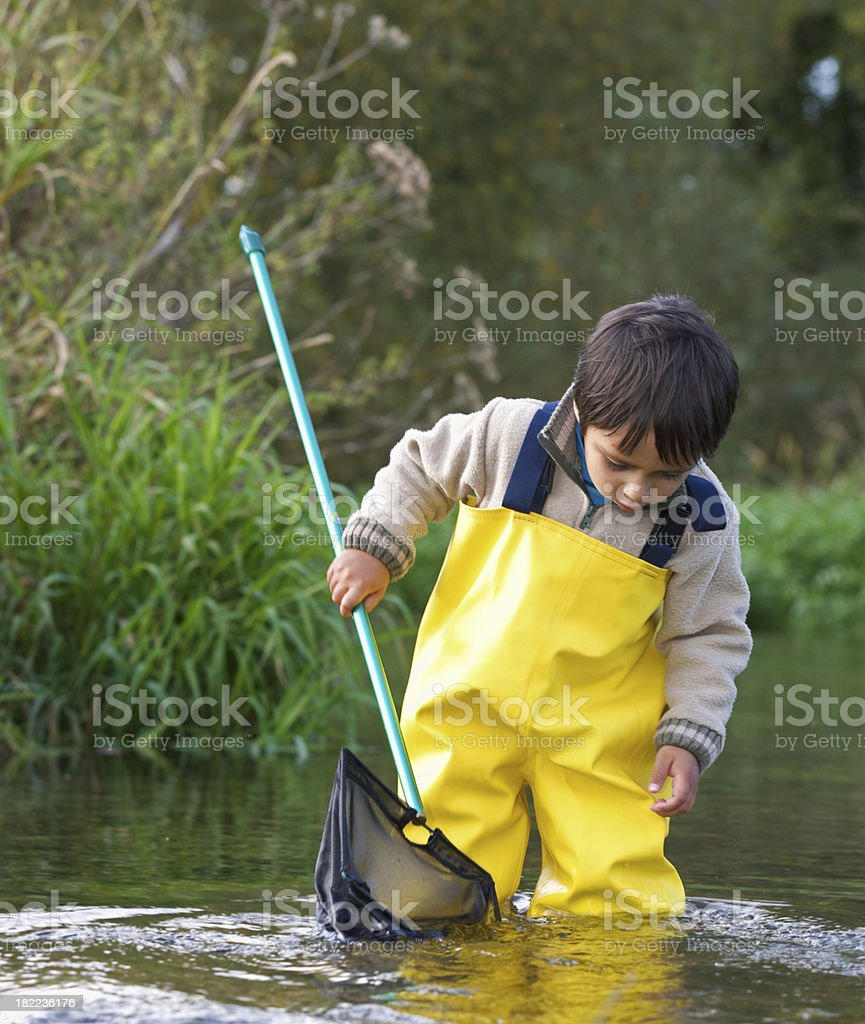 Young boy fishing in a stream stock photo