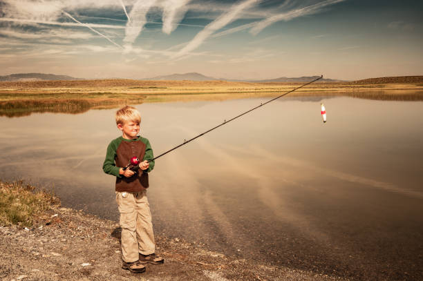 Young Boy Fishing In The Mountians stock photo