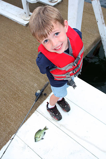 Young boy fishing on a dock stock photo