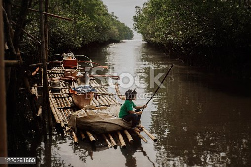 Young boy fishing with old-fashioned fishing rod on a bamboo raft.