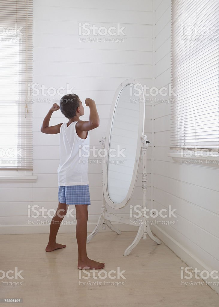 Young boy flexing his biceps in front of a mirror stock photo