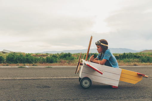 A young boy dressed in a flight cap and goggles gets ready to fly a vintage toy airplane. He is sitting in the plane as the pilot. Seeing sights from the sky has never been better. The boy is focused on the airplane runway ahead of him. Image taken in Utah, USA.